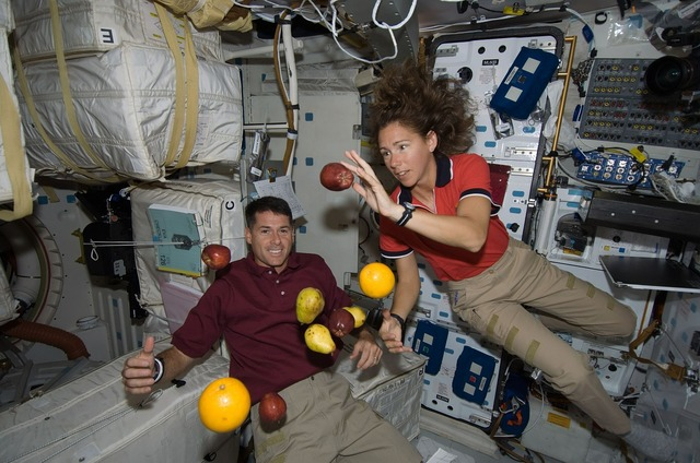 Astronauts floating fruit, food drink.