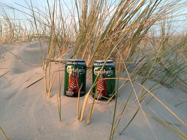 Beer cans beach dune, travel vacation.