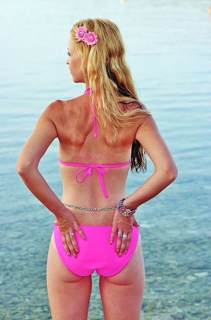 Blonde woman beach pink bathing suit, travel vacation.