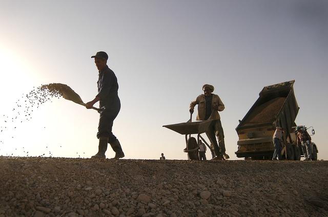 Construction workers shovel, transportation traffic.
