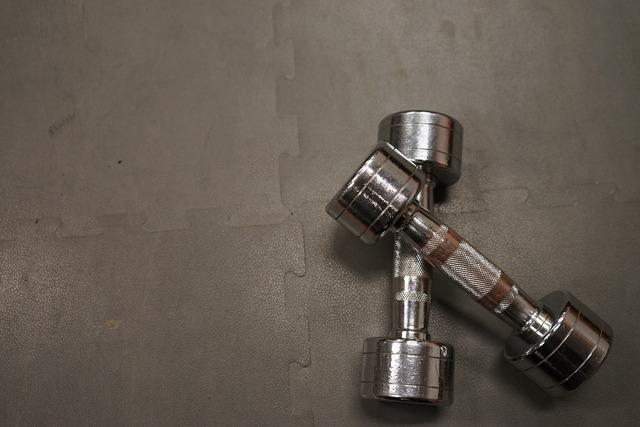 Dumbbells training silver, architecture buildings.