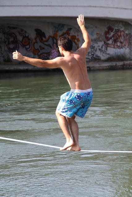 Equilibrist on naviglio, people.