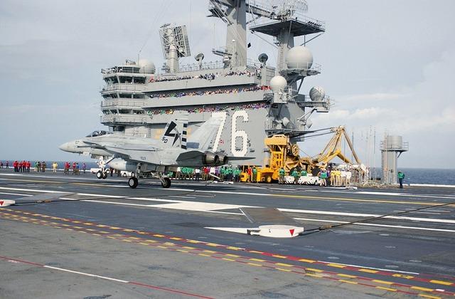 Fighter jet landing aircraft carrier.