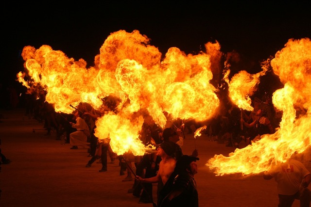 Fire eaters burning man flames.