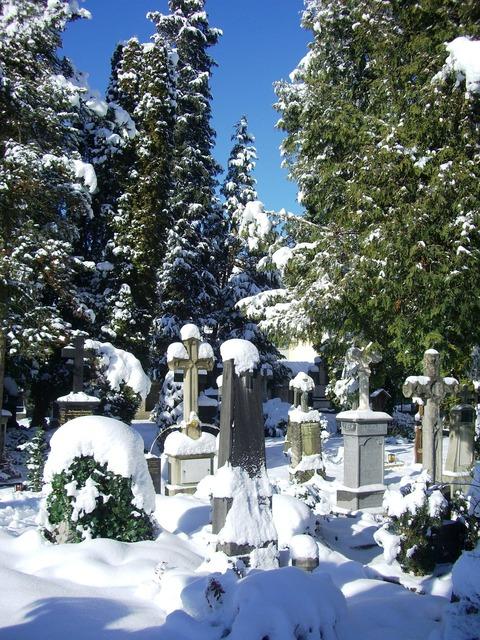 Grave stones snow caps old cemetery.
