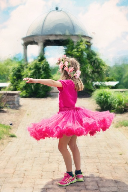 Little girl twirling dancing outdoors.