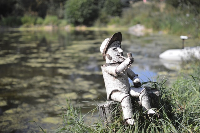 Little man wood doll water, nature landscapes.