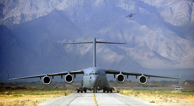 Military cargo plane takeoff runway mountains, transportation traffic.
