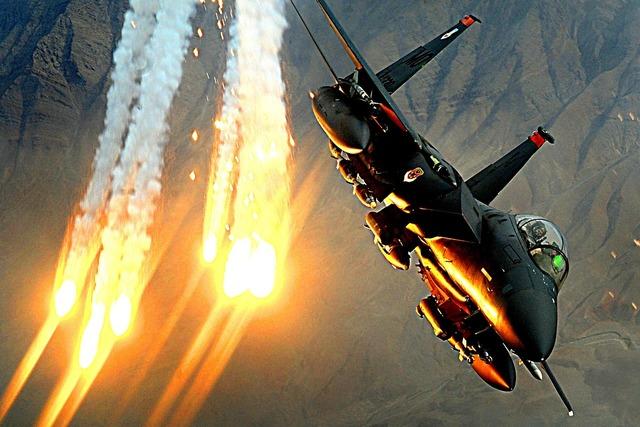Military jet flight launching heat decoys.