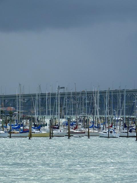 Port sailboats dark sky.