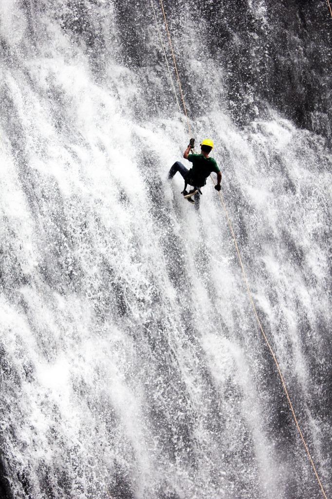 Rappelling waterfall adventure, people.