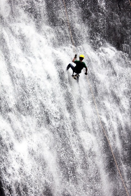 Rappelling waterfall adventure, people.