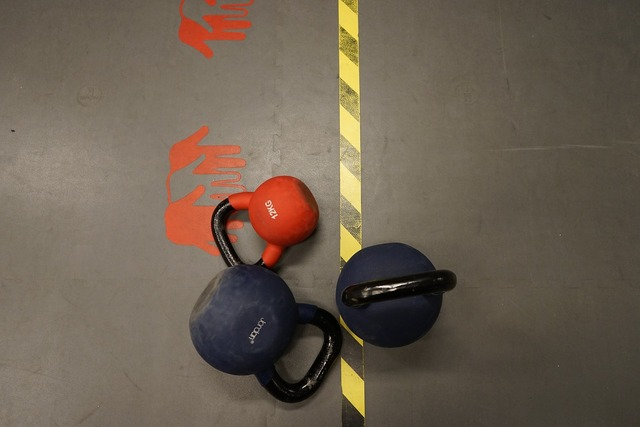 Red dumbbells training, architecture buildings.