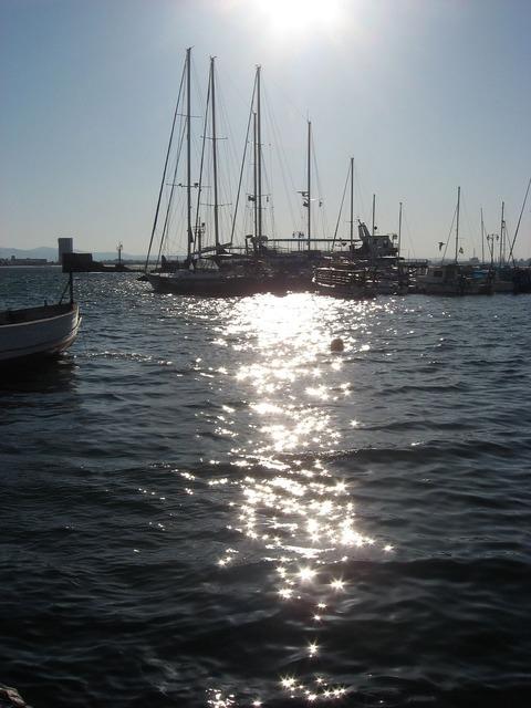 Sail boats ships sun.