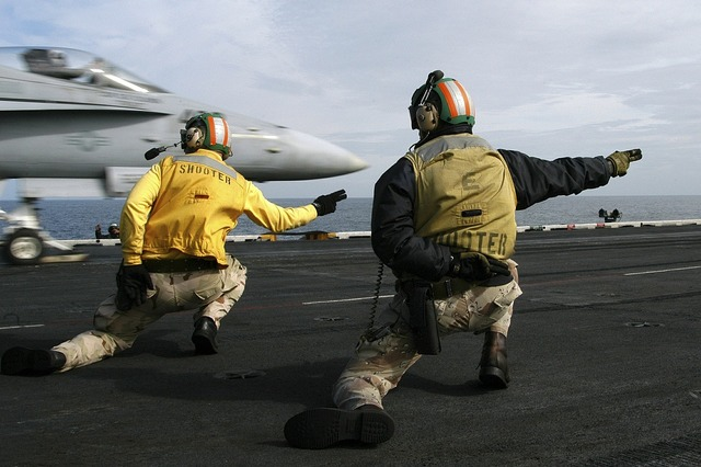 Sailors signal to launch jet aircraft carrier.