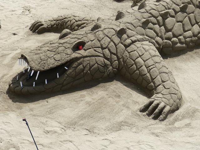 Sand sculpture alligator crocodile, travel vacation.