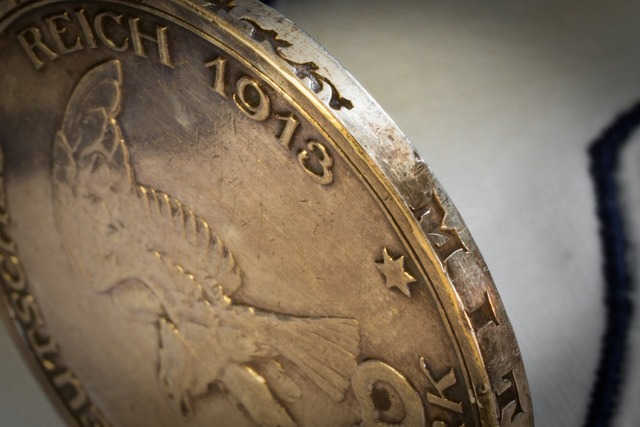 Silver coin edge embossing.