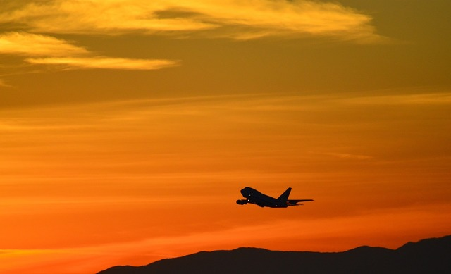 Sunset airplane silhouette, travel vacation.