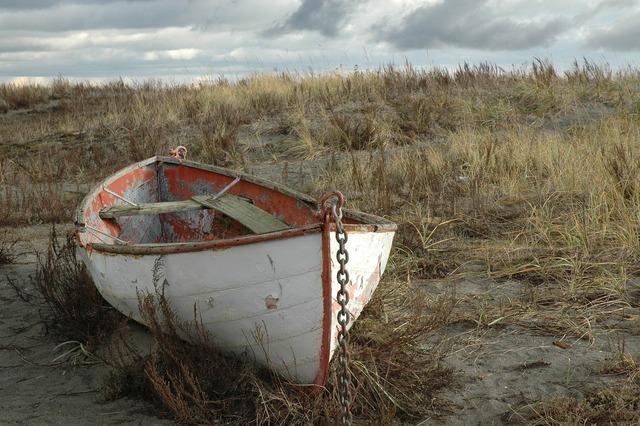 Weathered rowboat abandon boat beach, travel vacation.