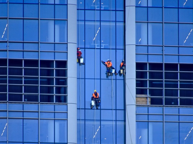 Window washer abseiling cleaning, architecture buildings.