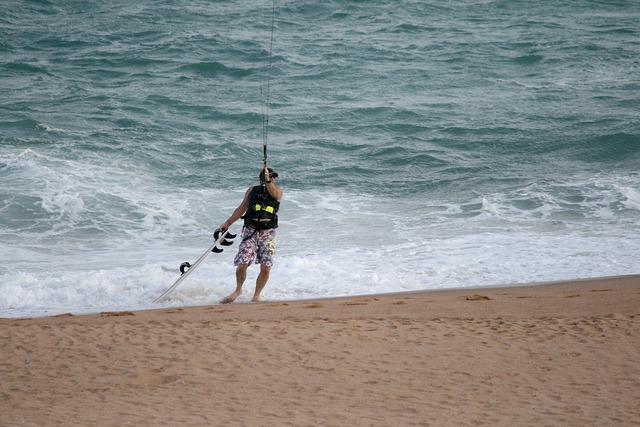 Windsurfer on beach beach sand, travel vacation.