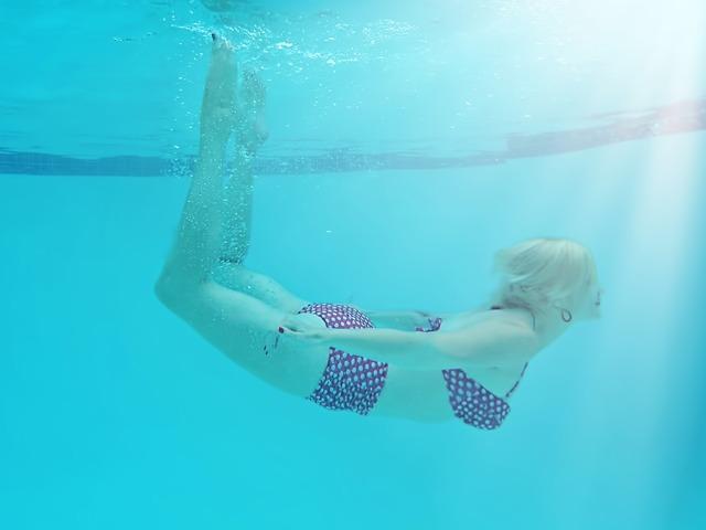 Woman underwater pool summer.