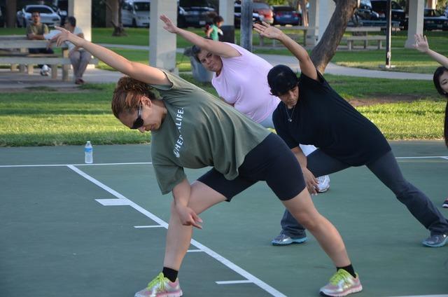 Women stretch outdoors, sports.