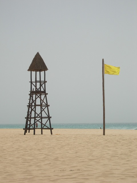 Yellow flag warning sandy beach, travel vacation.